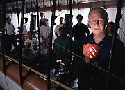 Dr. Paul MacCready, inventor and chairman of AeroVironment Inc., Simi Valley, California, with members of his staff in one of the company's cramped workrooms. Wing sections of the Centurion project aircraft hang from the ceiling. They are raised to save space when not being worked on. Robo sapiens Project.
