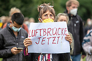"""A protester holds a banner reading """"Airlift Now"""" as people take part in a demonstration in front the Reichstag  building, seat of the German lower house of Parliament, the Bundestag in Berlin, Germany, August 17, 2021. About 1000 people gathered in front of the  under the call """"Airlift now! Create safe escape routes from Afghanistan!"""", the spontaneous event was organized by Seebrücke and several other human-rights organizations."""
