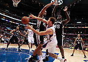 Los Angeles Clippers power forward Blake Griffin makes a pass around San Antonio Spurs center Tim Duncan, top left, and forward DeJuan Blair during the second half of an NBA basketball game Monday, Nov. 1, 2010, in Los Angeles. The Spurs won 97-88. (AP Photo/ Bret Hartman)