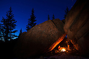 Marco Binotti (left) and David Coffey keep warm by a campfire in their cave camp in McMurdy Park, Lost Creek Wilderness, Colorado.