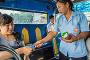 28 MARCH 2013 - BANGKOK, THAILAND: Michelle Kao pays her busfare after a day in the Thai Peace Foundation offices.      PHOTO BY JACK KURTZ