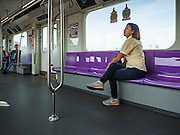 "23 AUGUST 2016 - NONTHABURI, NONTHABURI, THAILAND: A passenger in a nearly empty train car on the ""Purple Line,"" the new Bangkok commuter rail line that runs from Bang Sue, in Bangkok, to Nonthaburi, a large Bangkok suburb. The Purple Line is run by the  Metropolitan Rapid Transit (MRT) which operates Bangkok's subway system. The Purple Line is the fifth light rail mass transit line in Bangkok and is 23 kilometers long. The Purple Line opened on August 6 and so far ridership is below expectations. Only about 20,000 people a day are using the line; officials had estimated as many 70,000 people per day would use the line. The Purple Line was supposed to connect to the MRT's Blue Line, which goes into central Bangkok, but the line was opened before the connection was completed so commuters have to take a shuttle bus or taxi to the Blue Line station. The Thai government has ordered transit officials to come up with plans to increase ridership. Officials are looking at lowering fares and / or improving the connections between the two light rail lines.     PHOTO BY JACK KURTZ"