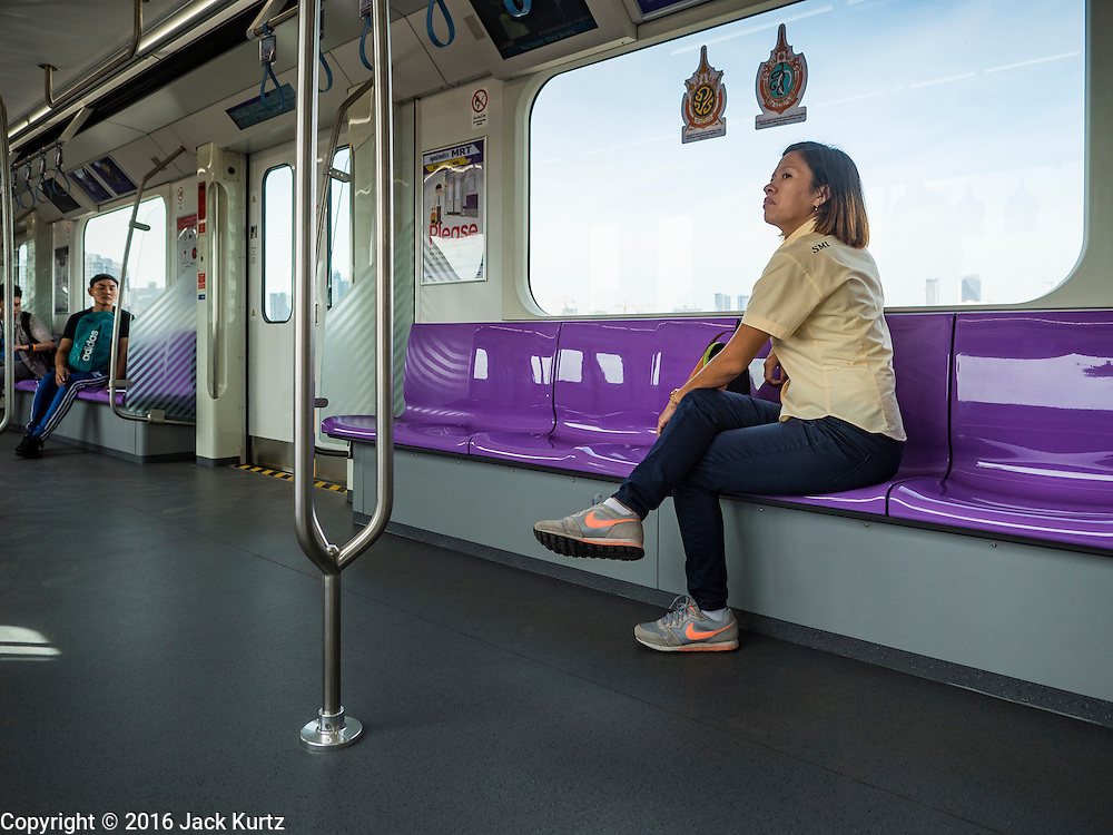 """23 AUGUST 2016 - NONTHABURI, NONTHABURI, THAILAND: A passenger in a nearly empty train car on the """"Purple Line,"""" the new Bangkok commuter rail line that runs from Bang Sue, in Bangkok, to Nonthaburi, a large Bangkok suburb. The Purple Line is run by the  Metropolitan Rapid Transit (MRT) which operates Bangkok's subway system. The Purple Line is the fifth light rail mass transit line in Bangkok and is 23 kilometers long. The Purple Line opened on August 6 and so far ridership is below expectations. Only about 20,000 people a day are using the line; officials had estimated as many 70,000 people per day would use the line. The Purple Line was supposed to connect to the MRT's Blue Line, which goes into central Bangkok, but the line was opened before the connection was completed so commuters have to take a shuttle bus or taxi to the Blue Line station. The Thai government has ordered transit officials to come up with plans to increase ridership. Officials are looking at lowering fares and / or improving the connections between the two light rail lines.     PHOTO BY JACK KURTZ"""