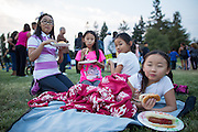 Abba Wu, 9, of San Jose enjoys a hot dog while laying down as her friends talk during the National Night Out event at Berryessa Creek Park in San Jose, California, on August 5, 2014. (Stan Olszewski/SOSKIphoto)