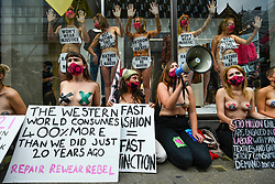 """© Licensed to London News Pictures. 09/09/2020. LONDON, UK.  Activists from Extinction Rebellion (XR) stage a """"Guerilla Repair"""" pop-up outside the H&M store on Oxford Street to protest against the environmental and human effects of fast fashion and disposable fashion. Some are have glued their hands to the inside of the shop window. Photo credit: Stephen Chung/LNP"""