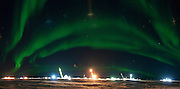 The aurora borealis forms a band above cranes driving pile for bridge construction across the Nigliq Channel at Alpine Oilfield, part of the CD5 drill site construction.
