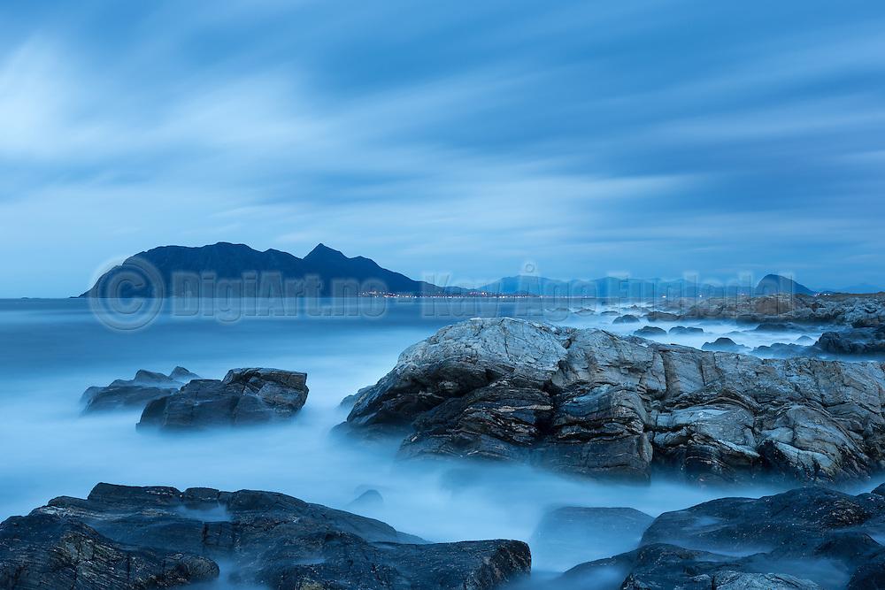 Seascape with long exposure gives a soft silky look in the sea and the sky. This picture is captured from Flø, Norway, and you can see the island Godøy in the background.  On the right far side, you see Sukkertoppen, nearby Ålesund | Sjølandskap med lang lukketid gir et mykt silkeaktig uttrykk på sjø og himmel. Bildet er tatt fra Flø, og du ser Godøya i bakgrunnen på venstre side, og Sukkertoppen ved Ålesund på høyreside.