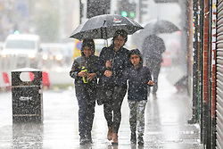 © Licensed to London News Pictures. 18/06/2020. London, UK. Members of the public shelter from heavy rain underneath an umbrella in north London.  Photo credit: Dinendra Haria/LNP
