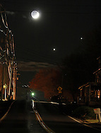 Goshen, NY -  The crescent moon, Venus, lower center, and Jupiter, at right, shine above a country road on the evening of Dec. 1, 2008.