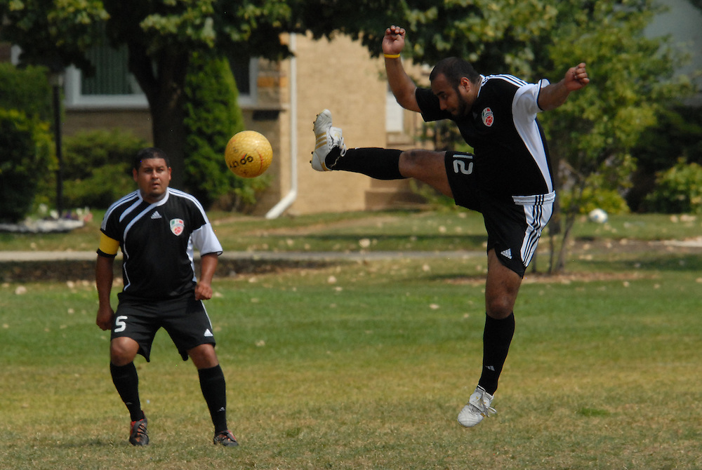 Emmanual Salgado (#12) gets airborne as teammate Ivan Rodriguez (#5) looks on as their undefeated Deportivo Colomex continues their winning way against Team Shlama F.C.