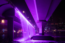 Illuminated waterfall from motorway bridge at night as part of the  Dubai Water Canal a waterway that connects into Dubai Creek and the sea. UAE, United Arab Emirates