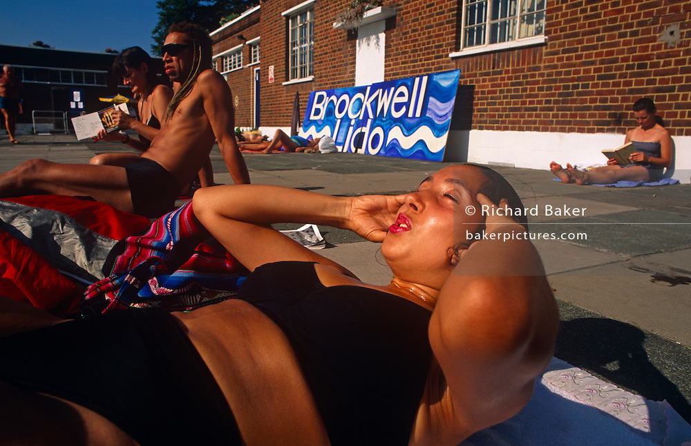 Breathing through her mouth, a lady wearing a bikini costume lifts her head supported with her hands to start another sit-up repetition during a morning exercise session at Brockwell Lido, Brixton South London. With other bathers also lying in sun on the warm poolside pavement, some white and another Rastafarian with dreadlocks, it's a largely mixed crowd ethnically. Brockwell Lido in Herne Hill SE24 was originally built in 1937 at a time of coastal and city pool-building but went into decline when bathers preferred to holiday in warmer Spain. Its revival happened when local entrepreneurs re-opened the business and it now enjoys a reputation for some of the best urban swims in the UK.