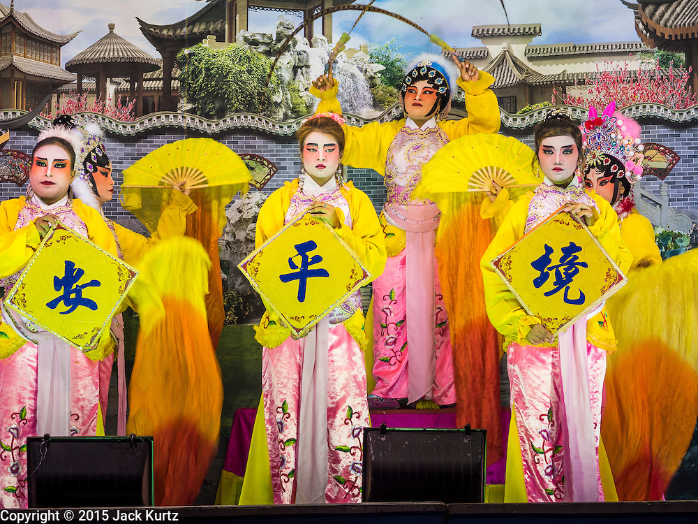 """14 MAY 2015 - BANGKOK, THAILAND: A Chinese opera performance at the Pek Leng Keng Mangkorn Khiew Shrine in the Khlong Toey slum in Bangkok. Chinese opera was once very popular in Thailand, where it is called """"Ngiew."""" It is usually performed in the Teochew language. Millions of Chinese emigrated to Thailand (then Siam) in the 18th and 19th centuries and brought their culture with them. Recently the popularity of ngiew has faded as people turn to performances of opera on DVD or movies. There are still as many 30 Chinese opera troupes left in Bangkok and its environs. They are especially busy during Chinese New Year and Chinese holiday when they travel from Chinese temple to Chinese temple performing on stages they put up in streets near the temple, sometimes sleeping on hammocks they sling under their stage. Most of the Chinese operas from Bangkok travel to Malaysia for Ghost Month, leaving just a few to perform in Bangkok.       PHOTO BY JACK KURTZ"""