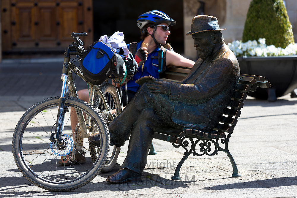Cyclist sits by bronze statue of architect Antoni Gaudi near Caja Espana in Leon, Castilla y Leon, Spain