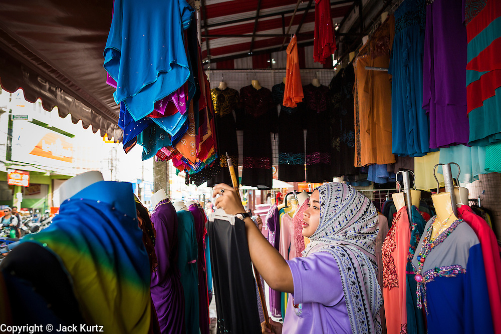 09 JULY 2013 - PATTANI, PATTANI, THAILAND: A woman hangs clothes she sells out for display in the market in Pattani.  Pattani, along with Narathiwat and Yala, are the only three Muslim majority provinces in Thailand.     PHOTO BY JACK KURTZ