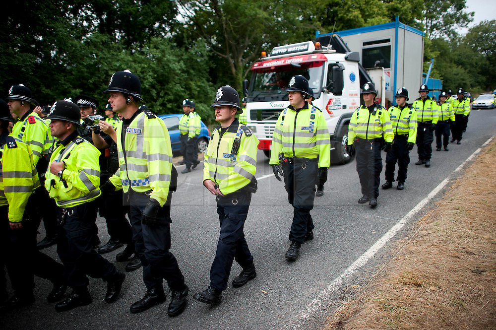 © London News Pictures. 16/08/2013. Balcombe, UK. Police guard a lorry waiting to enter the Cuadrilla drilling site in Balcombe, West Sussex which has been earmarked for fracking. Cuadrilla has temporarily ceased drilling at the site under advice from the police after campaign group No Dash For Gas threatened a weekend of civil disobedience. Photo credit: Ben Cawthra/LNP