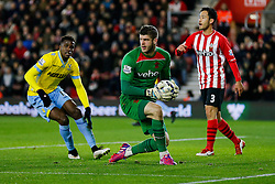 Fraser Forster of Southampton recovers after spilling the ball into the patch of Wilfried Zaha of Crystal Palace (L) - Photo mandatory by-line: Rogan Thomson/JMP - 07966 386802 - 03/03/2015 - SPORT - FOOTBALL - Southampton, England - St Mary's Stadium - Southampton v Crystal Palace - Barclays Premier League.