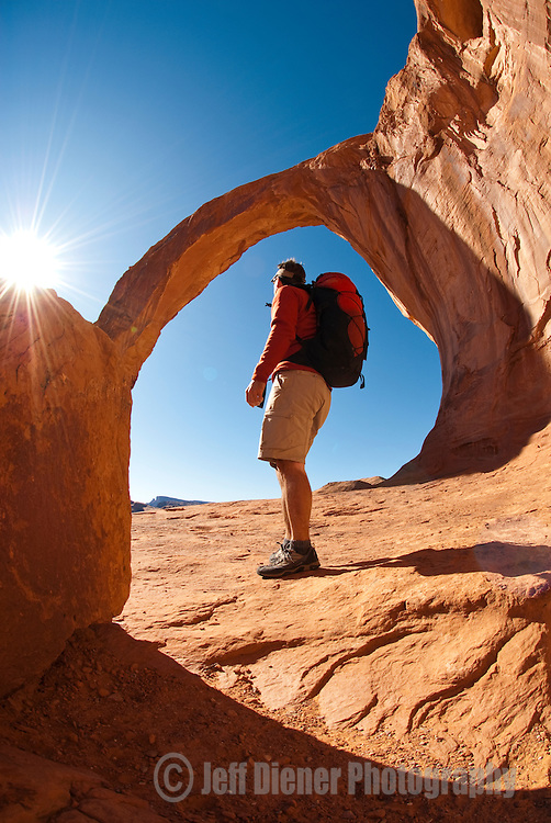 A young man admires the view while hiking below Corona Arch near Moab, Utah.
