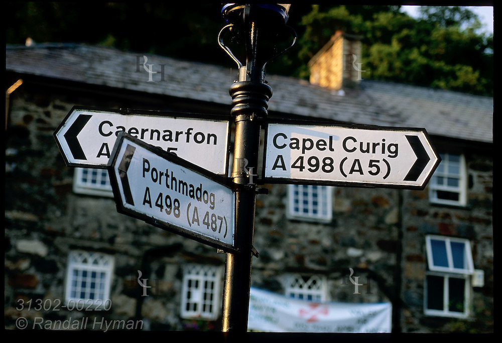 Road sign points in three directions toward three Snowdonia towns at crossroads in town of Beddgelert, Wales.