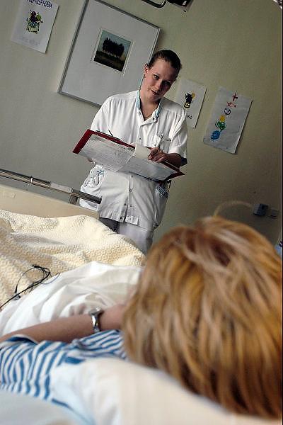 nederland, Nijmegen, 3-6-2003..Verpleegkundige werkt patientenstatus bij, van patient in ziekenhuis. Personeel aan bed in zorg. Toewijding, verzorging, personeelstekort, werkdruk, waardering, salaris...Foto: Flip Franssen