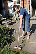 Model released image of teenage boy sweeping the yard