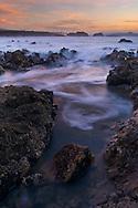 Waves moving through coastal rocks at low tide at sunset, Pescadero State Beach, San Mateo County coast, California