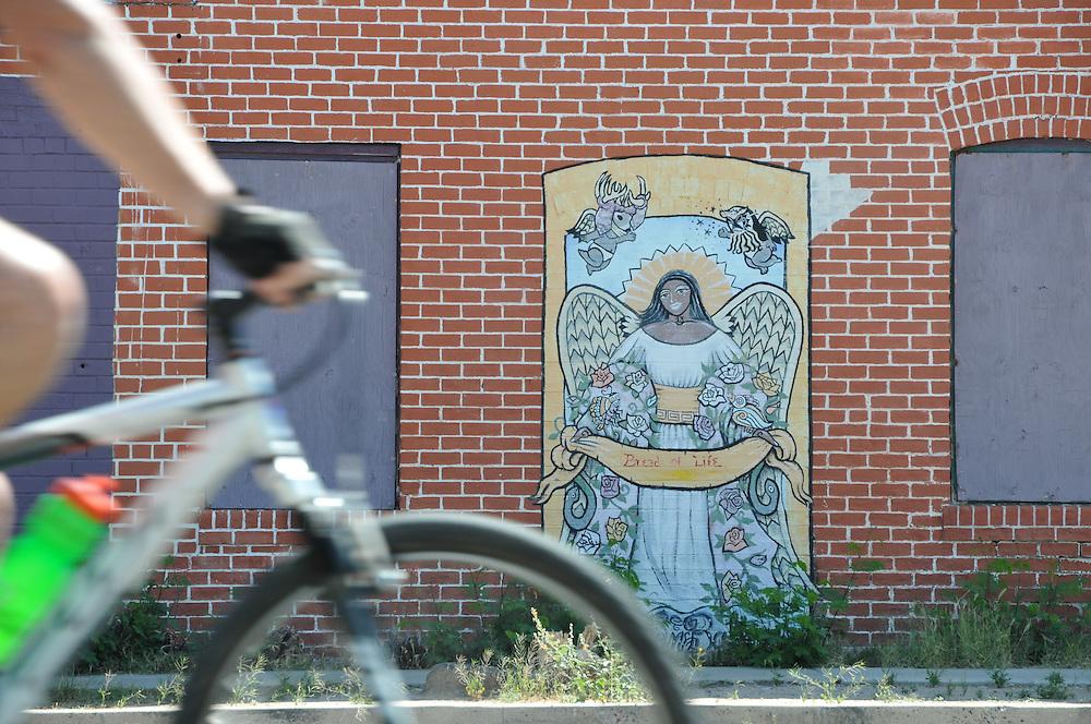 Rider passes mural on 4th Avenue during Cyclovia Tucson 2013. Bike-tography by Martha Retallick.
