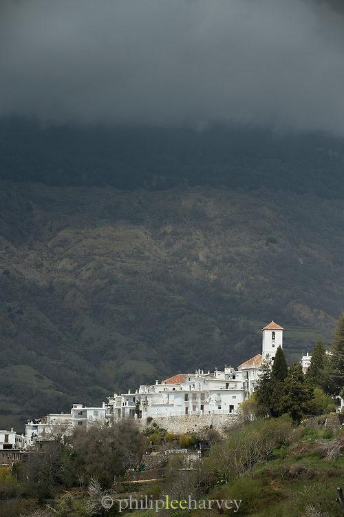 View of Bubion under storm clouds, Andalusia, Spain