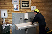 A school boy washes his hands on his way into class on his first day back in school after 4 weeks of corona lock-down, April 17th 2020,  Denmark. All schools and much of Denmark including its borders were shut Monday March 16th by the Danish Prime Minister Mette Frederiksen to prevent the corona virus from spreading beyond control. All school children had to stay at home if possible during the lock-down and many had not seen their friends through-out the 4 weeks it lasted. All teaching was done at home and via online services such as Google Meet and to many time was difficult to pass. Only year 0-5 are now allowed back in school and only under special measures. Classes are split in twos and across two rooms, everyone must wash hands rigorously when they leave and enter the class and the children must observe distance when possible. The children are put together in groups of no more than three and they are the only ones they get to work  and play with. Break time has to be in designated areas only and only with class mates.