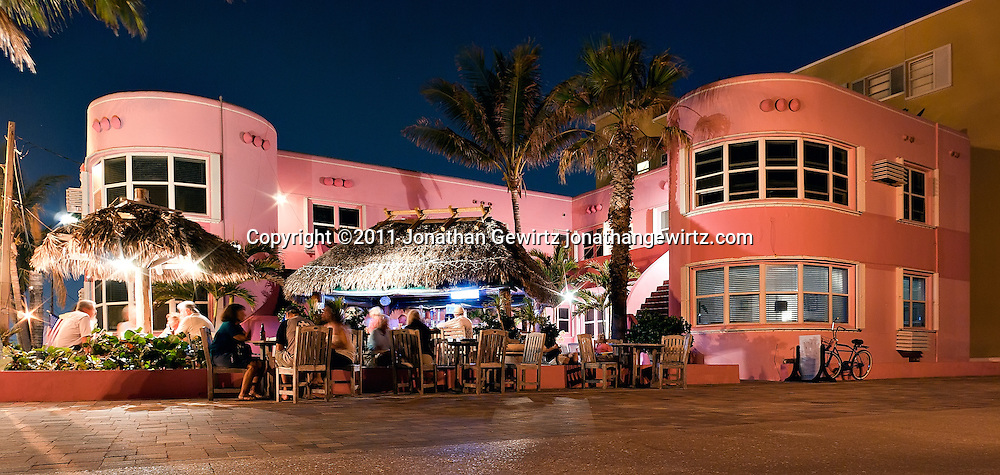 A night view of a small Art Deco apartment building on the Hollywood, Florida broadwalk. The building was built around 1950 and is currently in use as a resort. WATERMARKS WILL NOT APPEAR ON PRINTS OR LICENSED IMAGES.