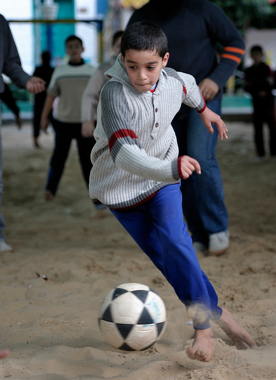 A boy plays football (soccer) in a center run by the Culture and Free Thought Association (CFTA), a Palestinian NGO in Khan Younis, in the Gaza Strip, which is supported by Christian Aid, a member of the ACT Alliance. The CFTA offers counseling and support for children affected by the Israeli blockade of Gaza, and provides a safe space to play, learn, and make friends. This work is critical for providing new hope to damaged children, both for their own sakes, and for the sake of the future of Palestinian society and a future peace with Israel..