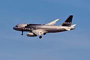 Spirit Airlines jet flying near LaGuardia Airport in New York City.