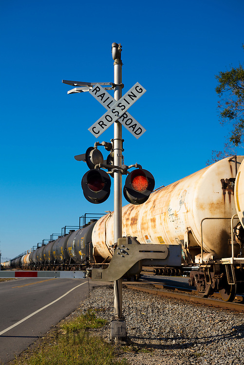 Freight train of tankers and carriages at railroad crossing with red traffic lights in Louisiana, USA