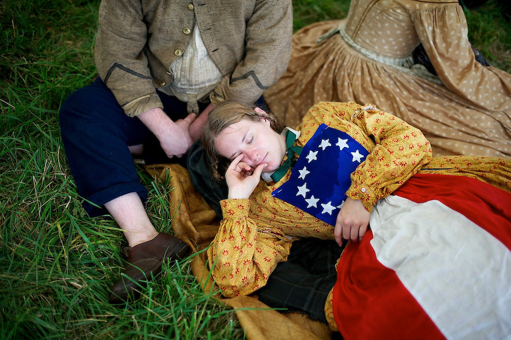 Wearing the 1st National Confederate Flag on her dress, Adrienne Robertson, from Richmond, VA, slumbers during a downpour at the 150th Antietam Civil War Reenactment in Boonsboro, Maryland on September 8, 2012.