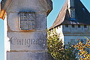 The gate post with a coat of arms and a stone carving saying Carignan - Chateau Carignan, Premieres Cotes de Bordeaux