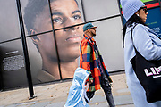 A child and an adult walk beneath the large billboard, a portrait of English football player, Marcus Rashford, outsidee the Strand branch of Coutts Bank, on 14th October, 2021, in Westminster, London, England. Marcus Rashford has recently been awarded an honourary degree by The University of Manchester in recognition of his political campaigning on behalf of the underprivilged (in particular, of school meals) and his philanthropy. He currently plays for Manchester United and is in the English national team. He has also been the victim of online racial abuse.