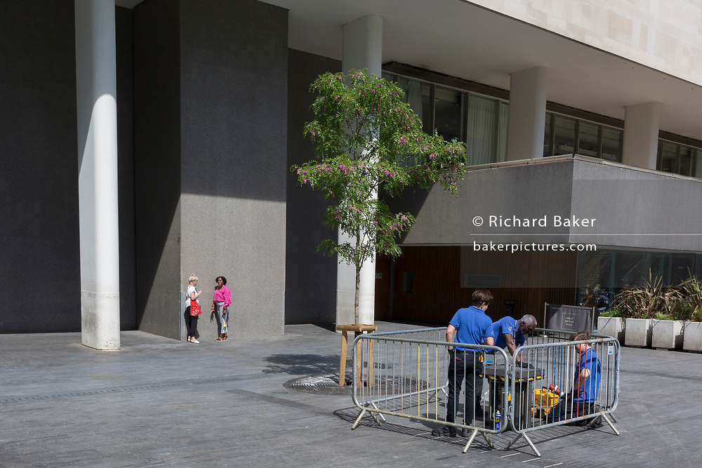 While workmen attend to a job, ladies take a sunshine break outside the Royal Festival Hall on the Southbank, on 9th May 2018, in London, England.