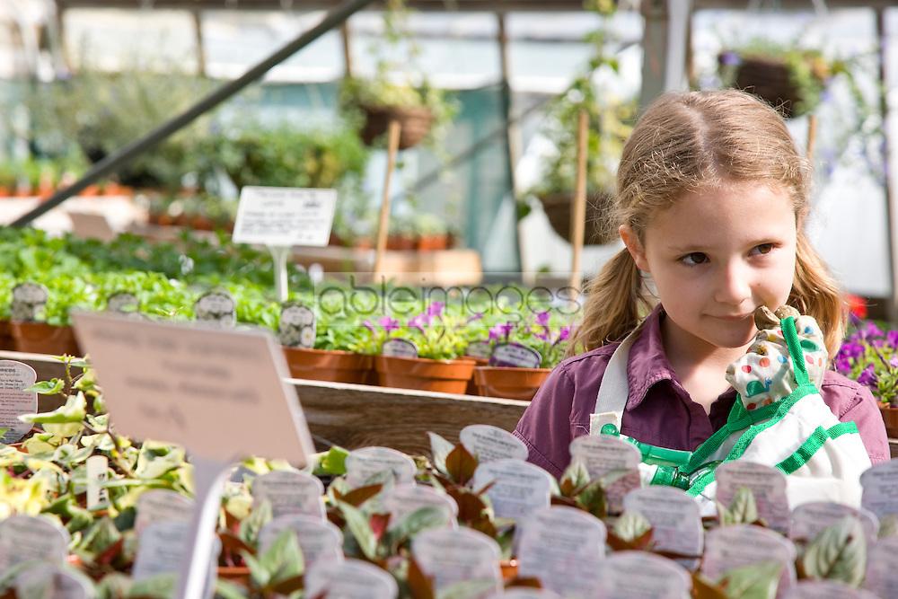 Portrait of young girl amongst flowerpots inside greenhouse