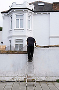 A man stands at the top of some stepladders to attend to the flat roof of a residential property in south London, on 15th September 2021, in London, England.