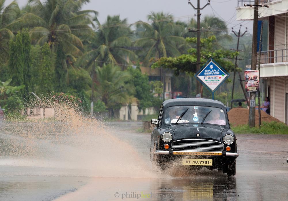 An Ambassador car driving during the monsoon rains, Cochin, Kerala, India.