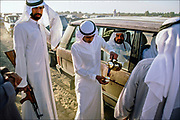 """In the outback of Sharjah, one of the seven sheikhdoms that make up the United Arab Emirates, a local leader arrives in a dust-covered convoy of family members and bodyguards for races at Al Dhaid Camel Race Track. Since child riders were outlawed in 2002, small robots are now used instead of humans in a move towards a """"more humane"""" form of racing in which winning purses can top $2 million. © Steve Raymer / National Geographic Creative"""