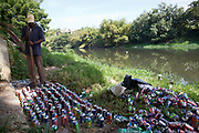 Cuban man homeless crushing hundreds of cans with a stick next to the river in a park, Havana.