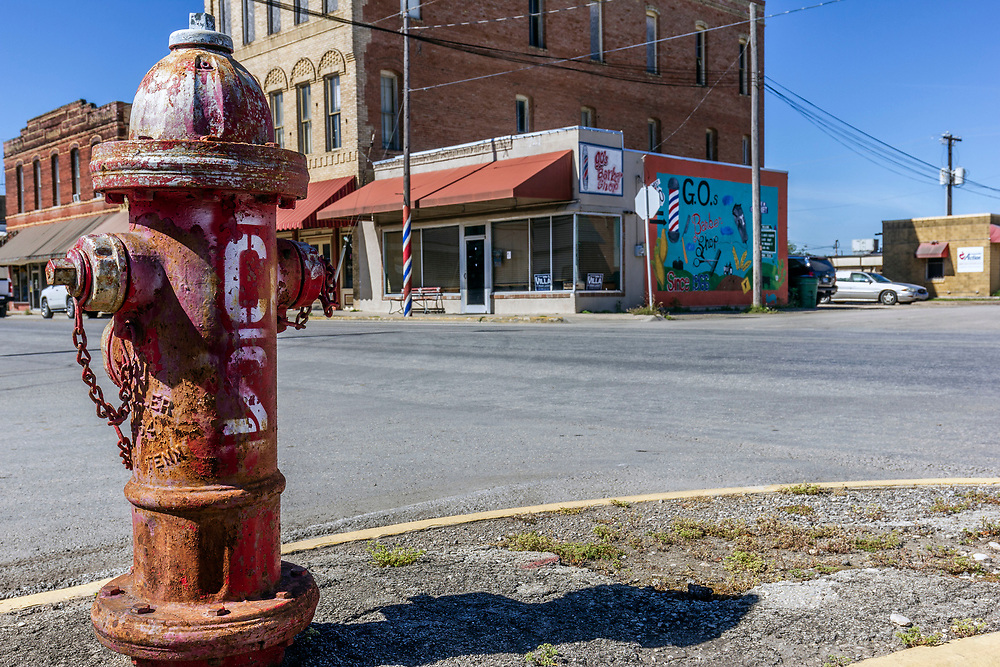 Downtown Hondo, with empty street, fire hydrant, shops and mural, Texas, USA.<br /> <br /> The original inhabitants of the area were the Coahuiltecan people in 1881 Non-indigenous settlers to the area came from Alsace-Lorraine, Germany, Belgium and Mexico. <br /> In the early 1920s, Hondo was the scene of two bank robberies carried out by the Newton Gang, the most successful outlaws in U.S. history. Both bank heists occurred the same night.