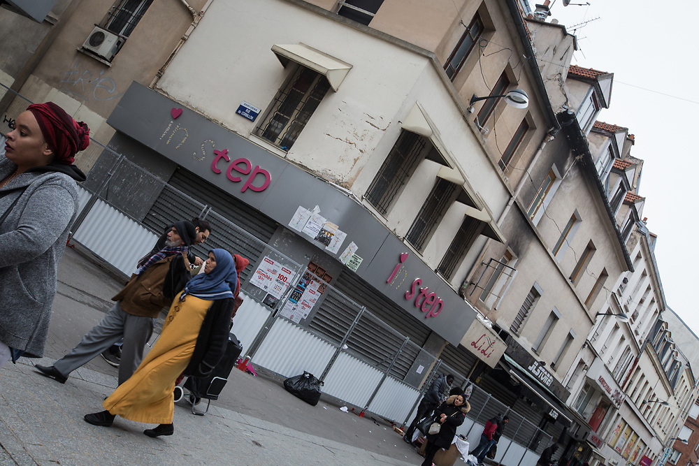 Pedestrians walk past a building located in the corner of Rue Corbillon and Rue de la Republique in the Paris suburb of Saint Denis.  The building served as refuge for Abdelhamid Abaaoud, the mastermind of the terrorist attacks commited on November 13, 2015.  The building has been closed off by the police since the attacks and most of its former residents await for permanent housing rrangements.   Saint Denis, France.  November 13, 2016.