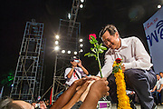 01 MARCH 2013 - BANGKOK, THAILAND: .A Thai politician accepts flowers from Pheu Thai supporters at the last election rally of the Bangkok governor race. The election is Sunday, March 3 and no campaigning is allowed 24 hours before election day. Police General Pongsapat Pongcharoen (retired), a former deputy national police chief who also served as secretary-general of the Narcotics Control Board is the Pheu Thai Party candidate in the upcoming Bangkok governor's election. He resigned from the police force to run for Governor. Former Prime Minister Thaksin Shinawatra reportedly personally recruited Pongsapat. Most of Thailand's reputable polls have reported that Pongsapat is leading in the race and likely to defeat Sukhumbhand Paribatra, the Thai Democrats' candidate and incumbent. The loss of Bangkok would be a serious blow to the Democrats, whose national base has been the Bangkok area.    PHOTO BY JACK KURTZ