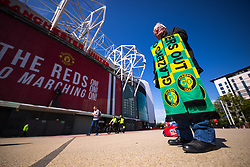 © Licensed to London News Pictures. 24/04/2021. Manchester , UK. Street peddler TOMMY CHOGGER (72) selling Glazers Out scarves on Sir Matt Busby Way . Manchester United Football Club fans are due to protest the decision of the club's owners to join a European super league, at the team's Old Trafford home . Arsenal, Chelsea, Liverpool, Manchester City, Manchester United and Spurs Football Clubs have all reversed their plans to join the new league following widespread outrage . Photo credit: Joel Goodman/LNP