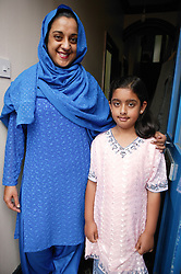 Mother and daughter standing in doorway of their home,