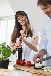 Mid adult woman opening wine bottle while mature man cutting vegetable, smiling