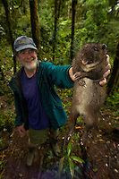 NGM writer Mel White holds up one of the Giant Rat species found in the Foja Mountains.