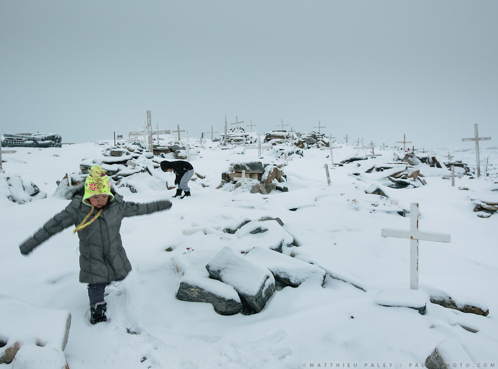 The day following a suicide, the children of hunter Magnus Enaksen are playing in the nearby graveyard. Life in and around the small Inuit settlement of Isortoq (population of 64), in East Greenland.